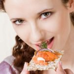 Young woman eating crispbread with salmon. Image shot 2009. Exact date unknown.